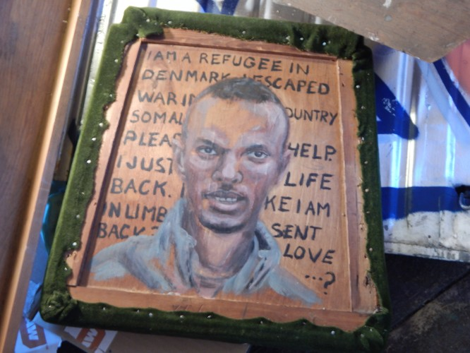 A refugee painted on a chair seat in a pile of refuse